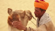 Rajasthani man loving his camel, Sam Desert, Jaisalmer, Rajasthan, India