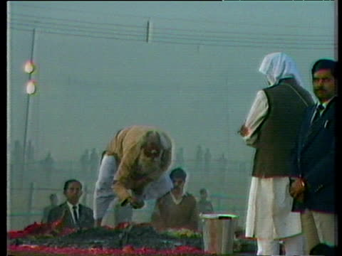 Rajiv Gandhi and pandit gather ashes and bone fragments from funeral pyre of Indira Gandhi Delhi Nov 84