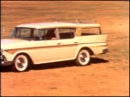 Ramblers and Ambassadors lined up on grassy field next to gravel road / WS tracking shot down row of cars we see the Rambler Six DeLuxe fourdoor...