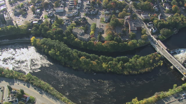 AERIAL Rapids below Pawtucket Falls on the Merrimack River, small city lining both riverbanks and bridges crossing / Lowell, Massachusetts, United States