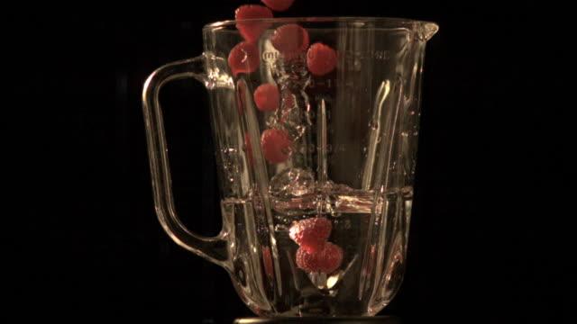 Raspberries falling into blender (slow motion)
