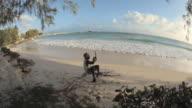 WS FISH EYE Rasta man on beach cutting and drinking coconut / Oistins, Christ Church, Barbados