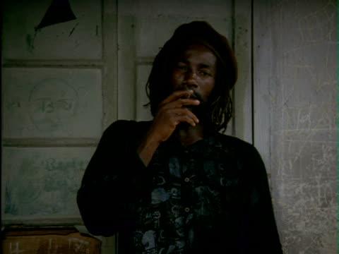 Rastafarian men wearing dreadlocks in backyard smoking marijuana from pipe and large joints Men smoking marijuana on January 01 1992 in Jamaica