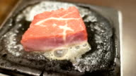 raw beef steak on a cast iron frying pan