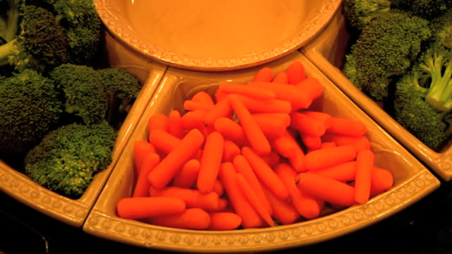 Raw broccoli florets on either side of gourmet Little Finger Carrots in divided ceramic serving dishes male fingers taking small carrot from tray...