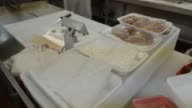 raw chicken being prepped on trays and then fed into an automatic wrapping machine at a supermarket in Princeton Illinois Food Manufacturing Chicken...