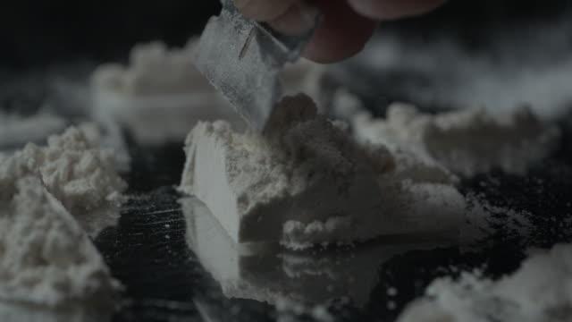 Razor blade cutting pile of cocaine