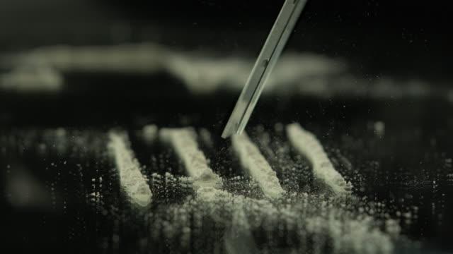Razor blade falls on lines of cocaine on mirror