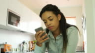 Reading phone message. Young woman, kitchen.