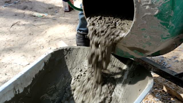 Ready concrete pours out of the concrete mixer into the wheelbarrow.