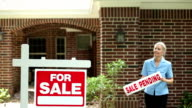 Real estate agent places 'sale pending' sign. Home for sale.