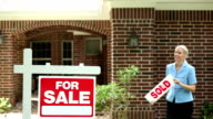 Real estate agent places sold sign on home for sale.