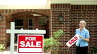 Agente immobiliare luoghi venduto casa per segno di vendita.