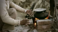 Real people from rural India: Man cooking food on bonfire