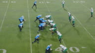 WS Real Time. Aerial view. Professional football teams break huddle and come to line of scrimmage, quarterback throws an interception and receiving player runs ball out of bounds and celebrates turnover with teammates.