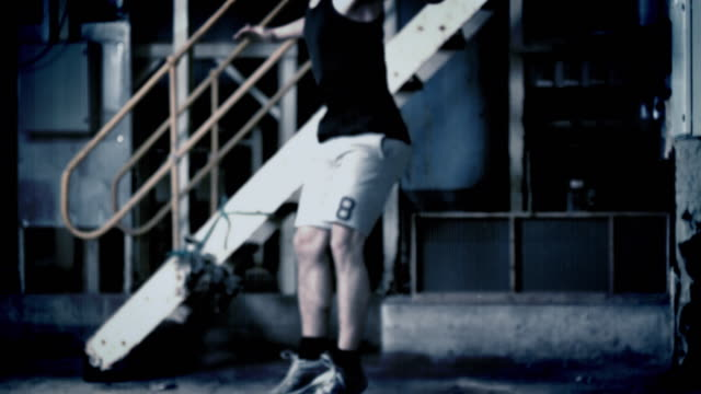 Real time and slow motion footage of a man jumping down a staircase in a warehouse