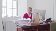 Real time video of businessman receiving good news on an e-mail in the office