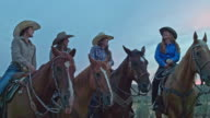 Real time video of cowgirls talking and having fun enjoying horseback riding in the fields at dusk