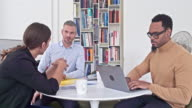 Real time video of three businessmen discussing in creative office