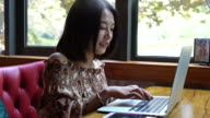 Real Time Young smiling Asian girl is playing laptop and enjoying coffee in cafe