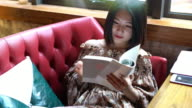 Real Time Young smiling Asian girl reading and enjoying coffee in cafe