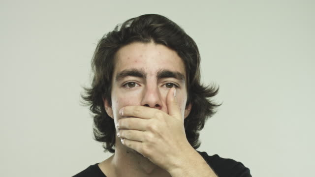 Real young man covering eyes, ears and mouth with hands