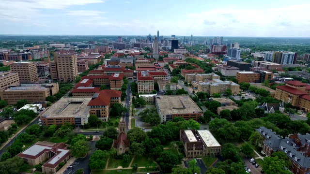 Really Far Wide Angle Campus UT Tower Aerial Fly by Austin Texas Over University of Texas at Austin Capital Cities with Downtown Cityscape Skyline in the background at Center moving forwards close with Pool and Amazing Architecture and Church in View