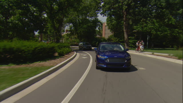 Rear POV of a college student driving a blue sedan through the campus of Michigan State University.