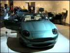 WS rear end of DB7 V12 Vantage convertible revolving on turntable below Aston Martin sign on wall / WS HA DB7 convertible front end / MWS front...