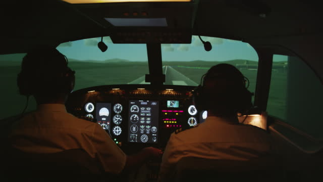 MS rear internal view of pilots and instrument panel in professional flight simulator during landing, RED R3D 4K