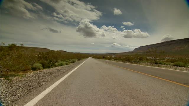 WS DRIVING Down unidentified road through desert passing rocks shrubs in sand pulling over white truck passes mountains BG