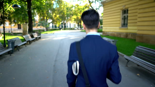 Rear shot view of one young businessman walking on the street and holding newspaper under his arm.