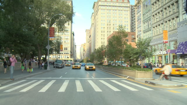 POV Rear view from car driving down street with taxis / New York City, New York, United States