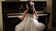 TU Rear view girl in white dress playing piano turns and smile