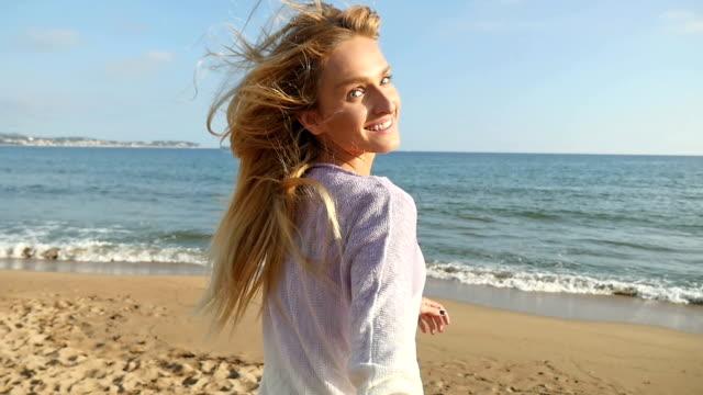 Achteraanzicht van een gelukkige vrouw lopen op het strand