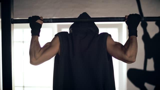 Rückansicht eines Mannes training auf Klimmzugstange