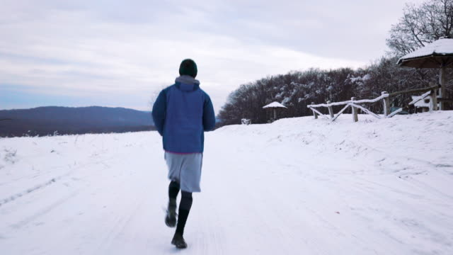 Rear view of athletic man running in nature during cold winter day.