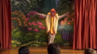 Rear view of audience watching curtains part at beginning of school play / boy in hot dog costume dancing on stage / girls in pea pod and carrot costumes entering and shooing boy off stage / mother rising and taking pictures / girls bowing before audience