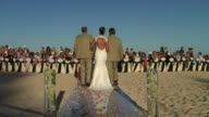 WS, CS, Rear view of bride walking down aisle with two men, beach of Cabo San Lucas, Mexico