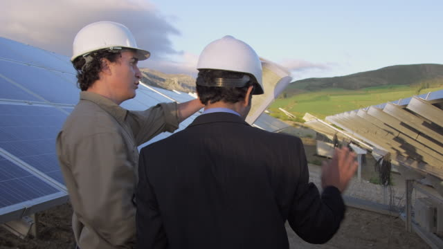 CU Rear view of businessman and engineer walking through photovoltaic (solar) plant, discussing project / Malaga, Spain