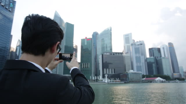 MS Rear View of businessman taking a photo of the city with his phone