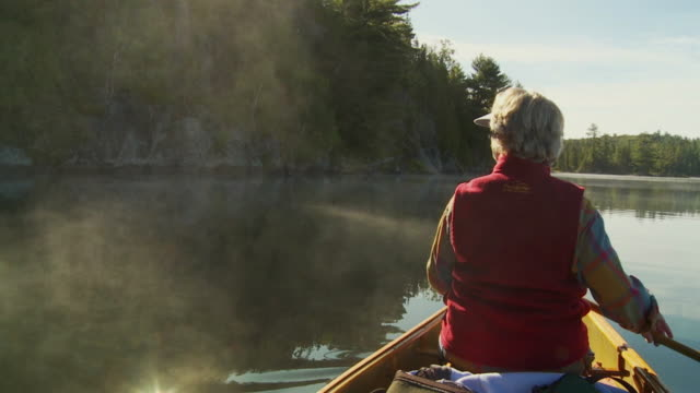 SLO MO MS Rear view of canoeist on lake at sunrise, Algonquin Park / Whitney, Ontario, Canada