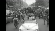 MLS rear view of car and crowds along motorcade route in Harlem on 'Josephine Baker Day' / WS elevated view of opentop car carrying singer Josephine...