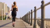 Rear view of Caucasian teenage girl running on boardwalk