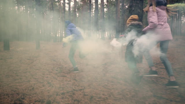 Rear view of children running with smoke bombs in forest