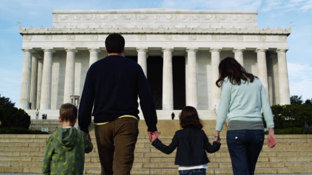 WS Rear view of family with two children (4-5, 6-7) ascending steps at Abraham Lincoln Memorial / Washington DC, USA