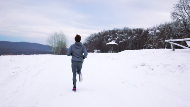 Rear view of female athlete running on a snow in nature.