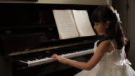 MS Rear view of girl wearing white dress, playing piano / China