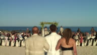 WS, CS, Rear view of groom walking down aisle with parents, beach of Cabo San Lucas, Mexico