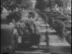 Rear view of jeep carrying Franklin D Roosevelt driving past military personnel / view of Roosevelt in jeep from moving vehicle / Roosevelt and...
